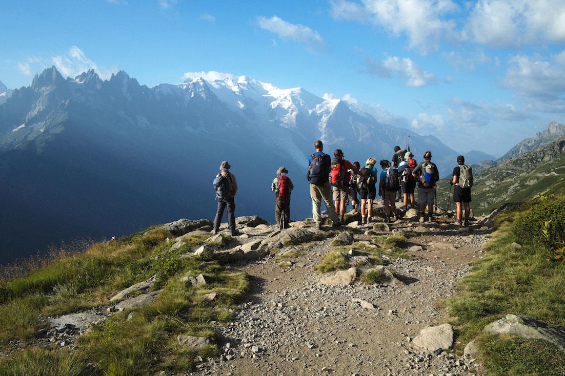 Grupo de montanhistas observa um grande vale e montanhas com neve.