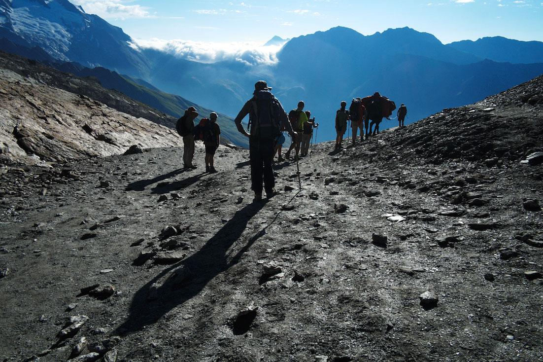 Montanhistas num col de terra negra com vistas deslumbrantes sobre os vales no maciço do monte branco.