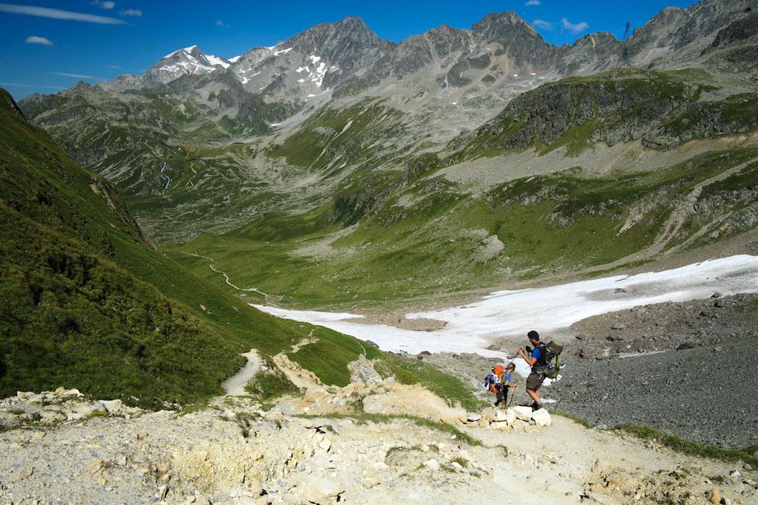 Montanhistas descem uma vertente acentuada, ainda com neve, no tour do monte branco.