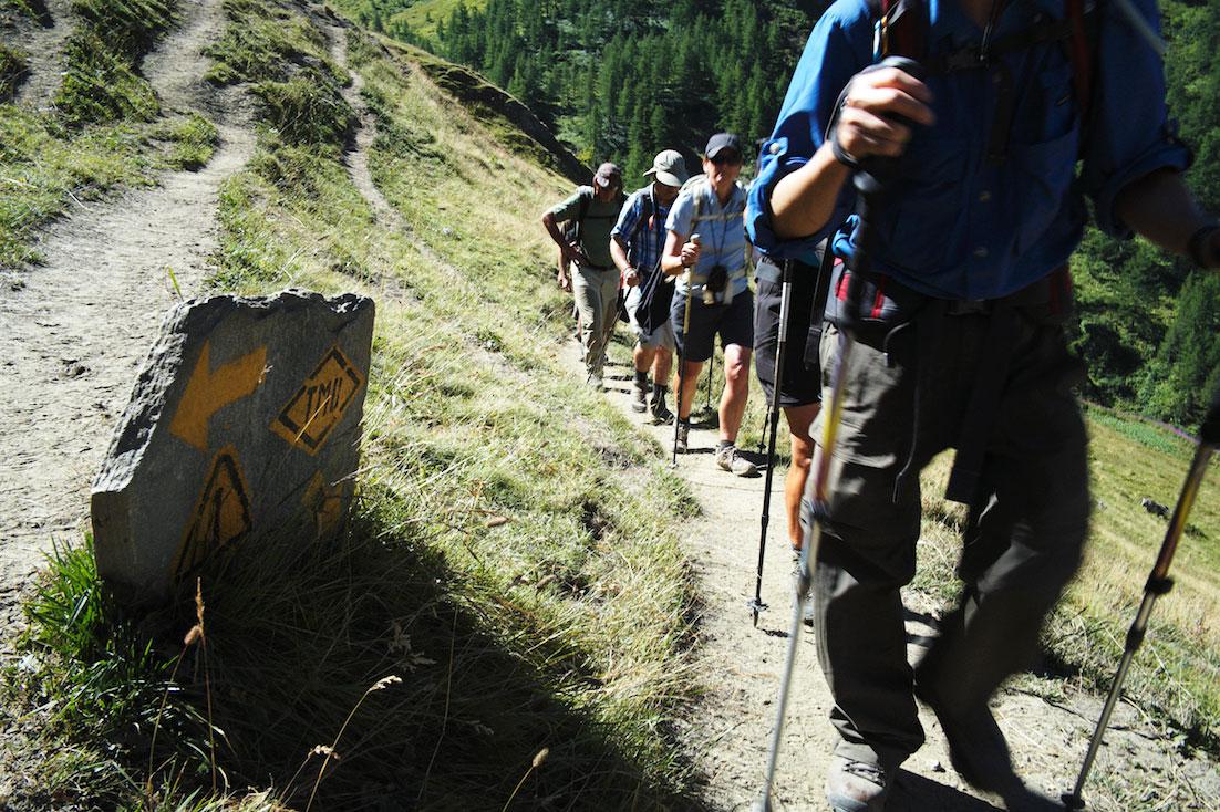 Montanhistas passam aceleradamente junto a placa indicativa de percurso no maciço do monte branco.