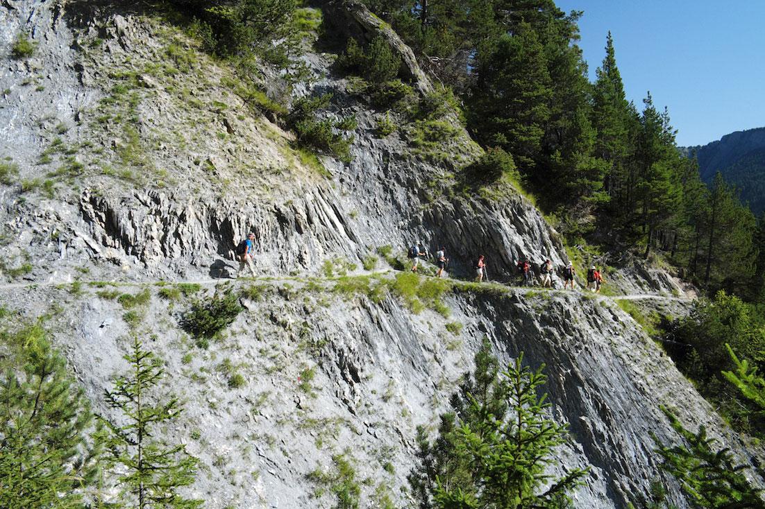 Montanhistas percorrem trilho sobranceiro a uma ravina pedregosa.