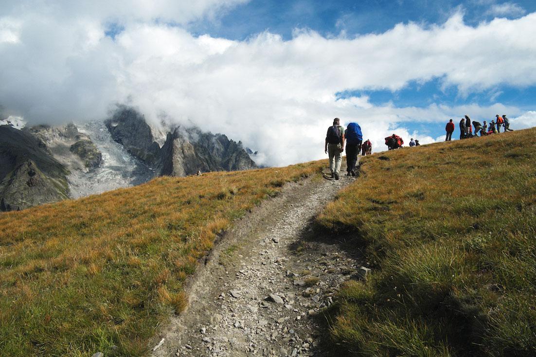Grupo de montanhistas percorre um trilho acentuado, debaixo de um céu nublado, no maciço do monte branco.