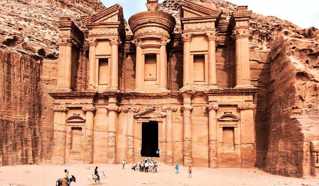 Mulas e grupos de pessoas em frente ao templo Mosteiro em Petra.