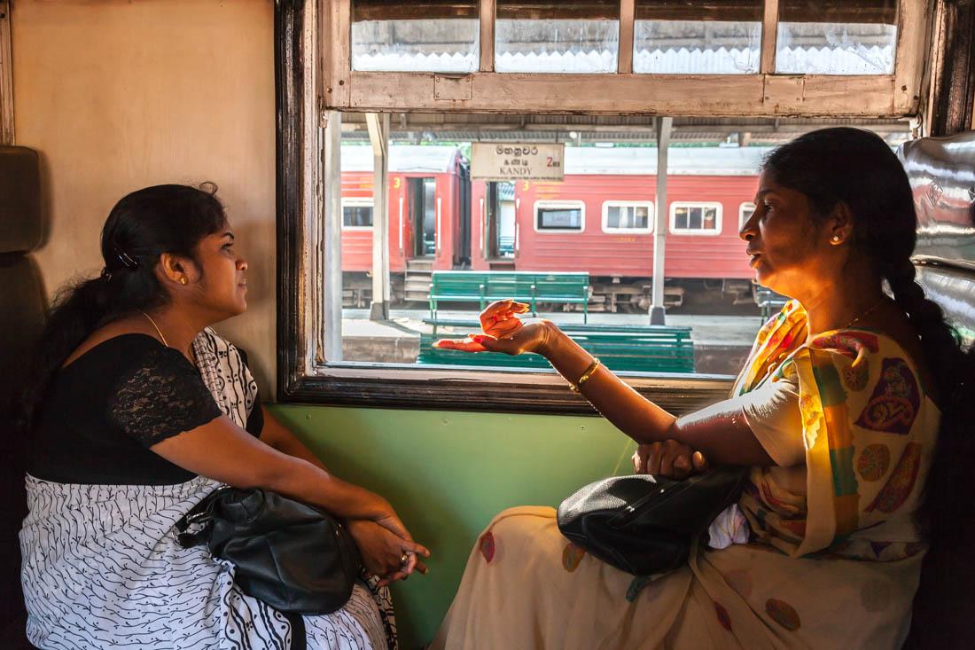 Mulheres a conversar sentadas num comboio na estação de Kandy, Sri Lanka.