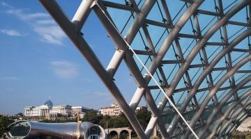 Parlamento de Tbilisi, capital da Geórgia, por entre várias estruturas metálicas modernistas.