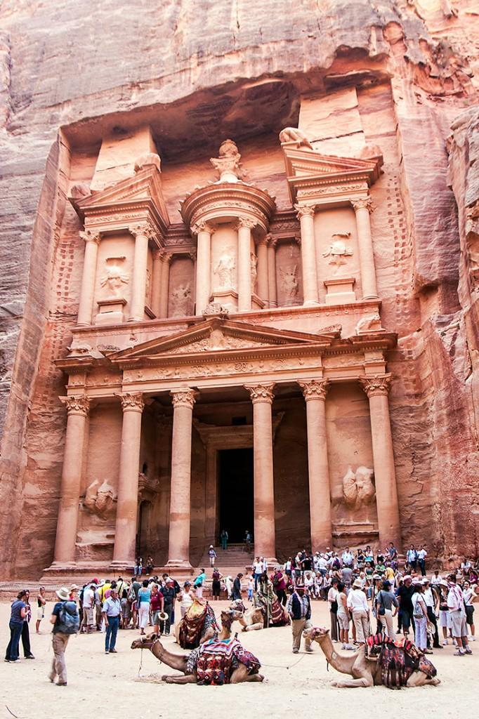 Grupos de pessoas e camelos frente ao Tesouro em Petra, na Jordânia.