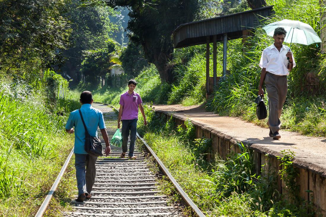 Pessoas a caminhar sobre a linha de caminho-de-ferro numa zona da cidade de Kandy, Sri Lanka.