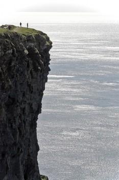 Duas pessoas junto à berma de um grande penhasco dos Cliffs of Moher.