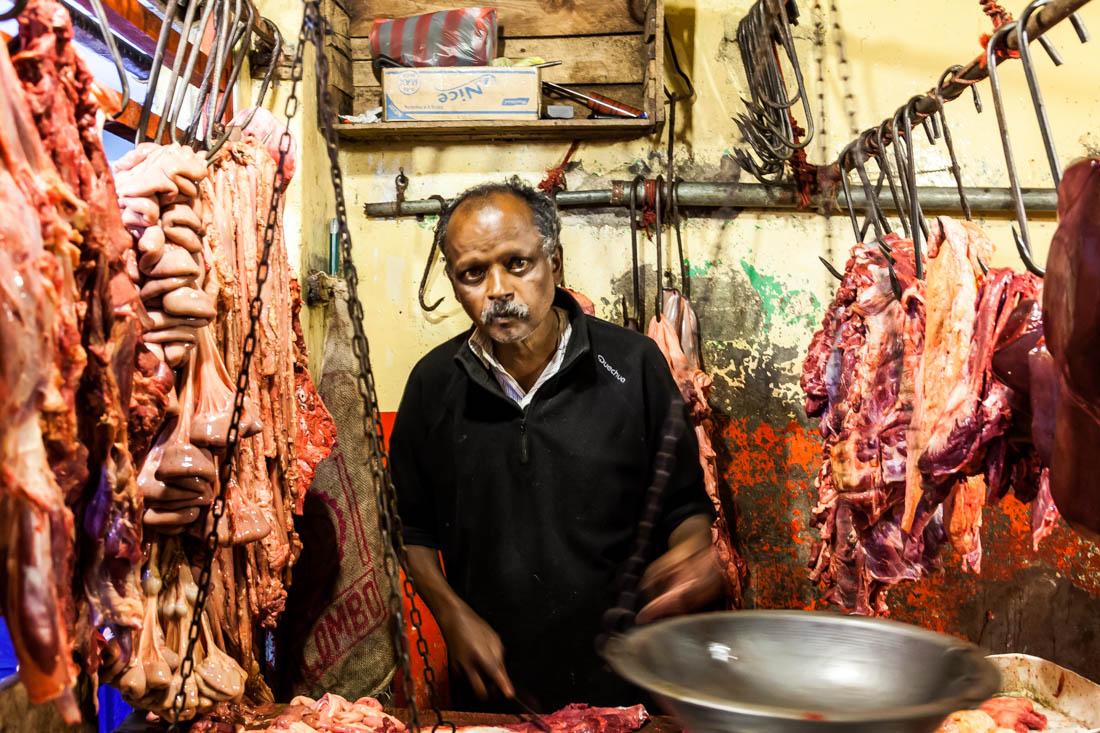 Homem talhante com muita carne pendurada em ganchos de um talho no mercado de Nuwara Eliya no Sri Lanka.