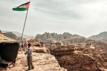 Bandeiras jordanas e tendas de chá com com vista para wadi araba perto do Mosteiro em Petra.