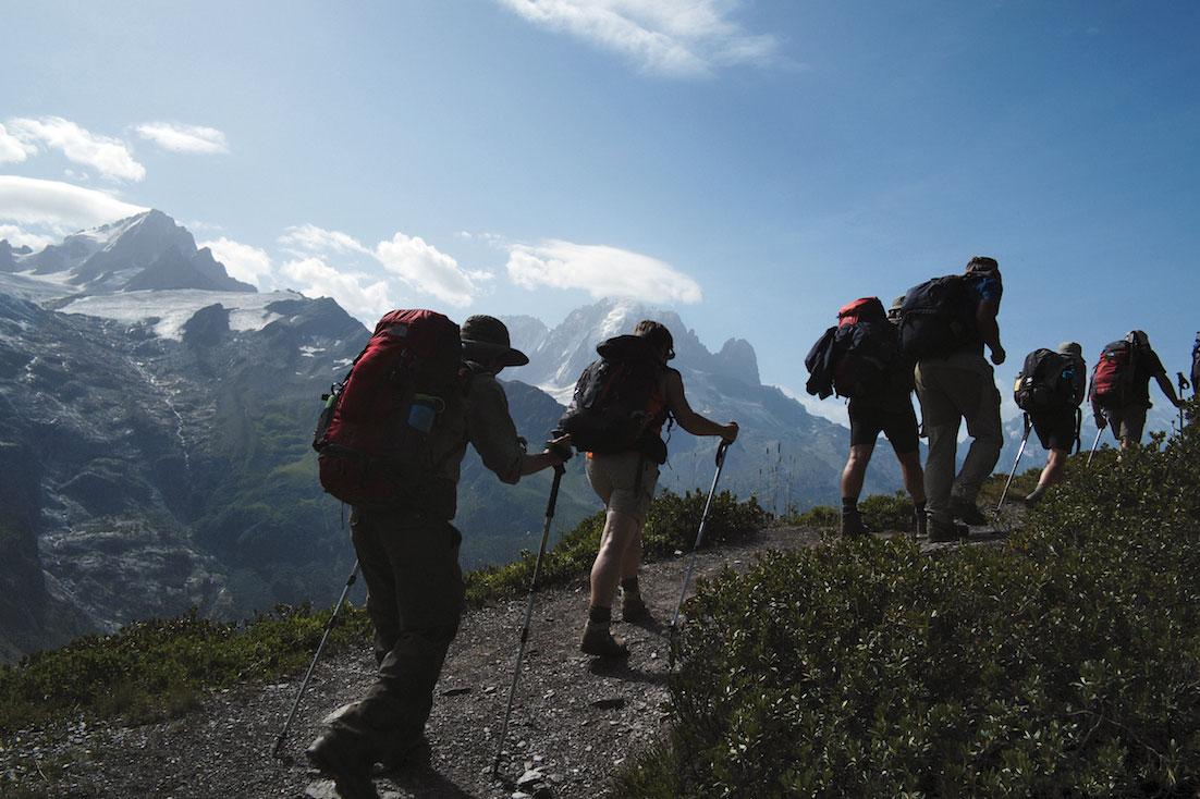 Montanhistas num trilho com vista para os picos do monte branco ainda nevados.