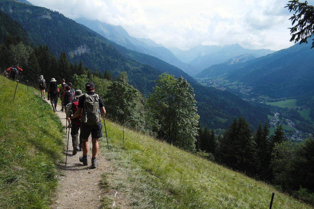 Trilho da paisagem alpina com vista para aldeias de um vale.