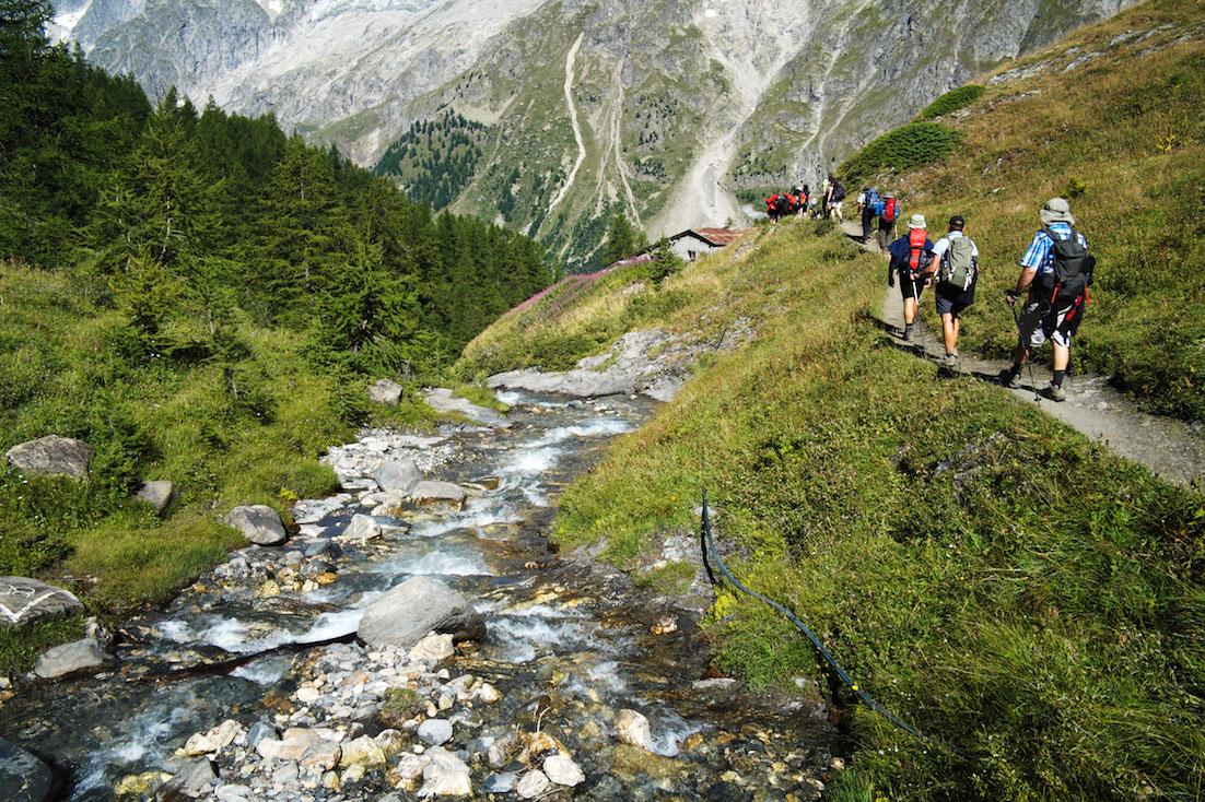 Montanhistas num trilho alpino paralelo a ribeiro de água cristalina.