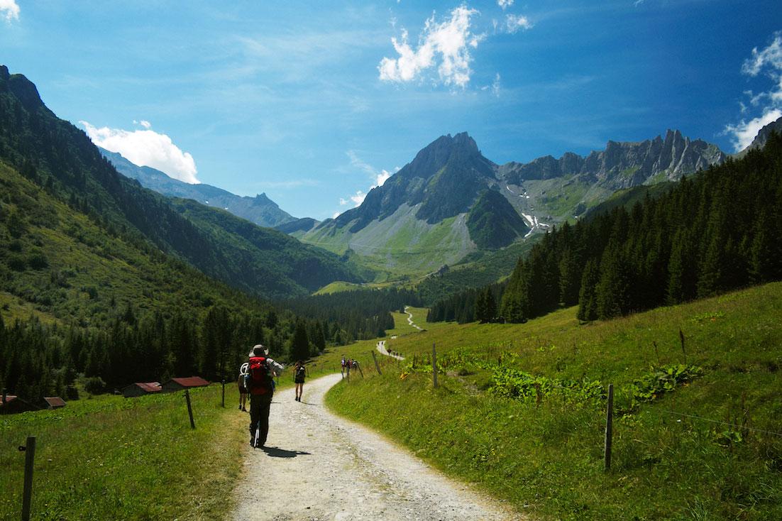 Paisagem verde alpina atravessada por montanhistas num dos trilhos do Tour do Monte Branco.
