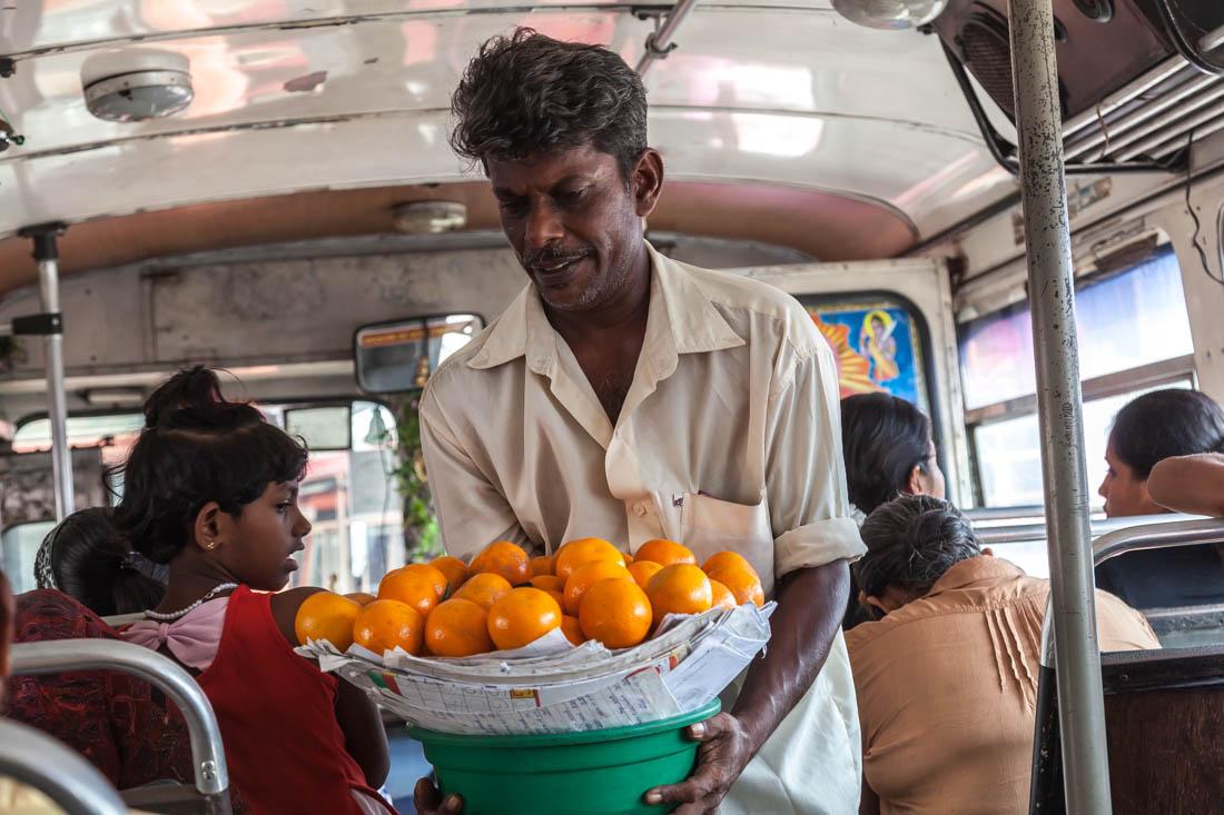 Homem vendedor de laranjas no autocarro que liga a cidade de Galle e a Praia de Unawatuna.