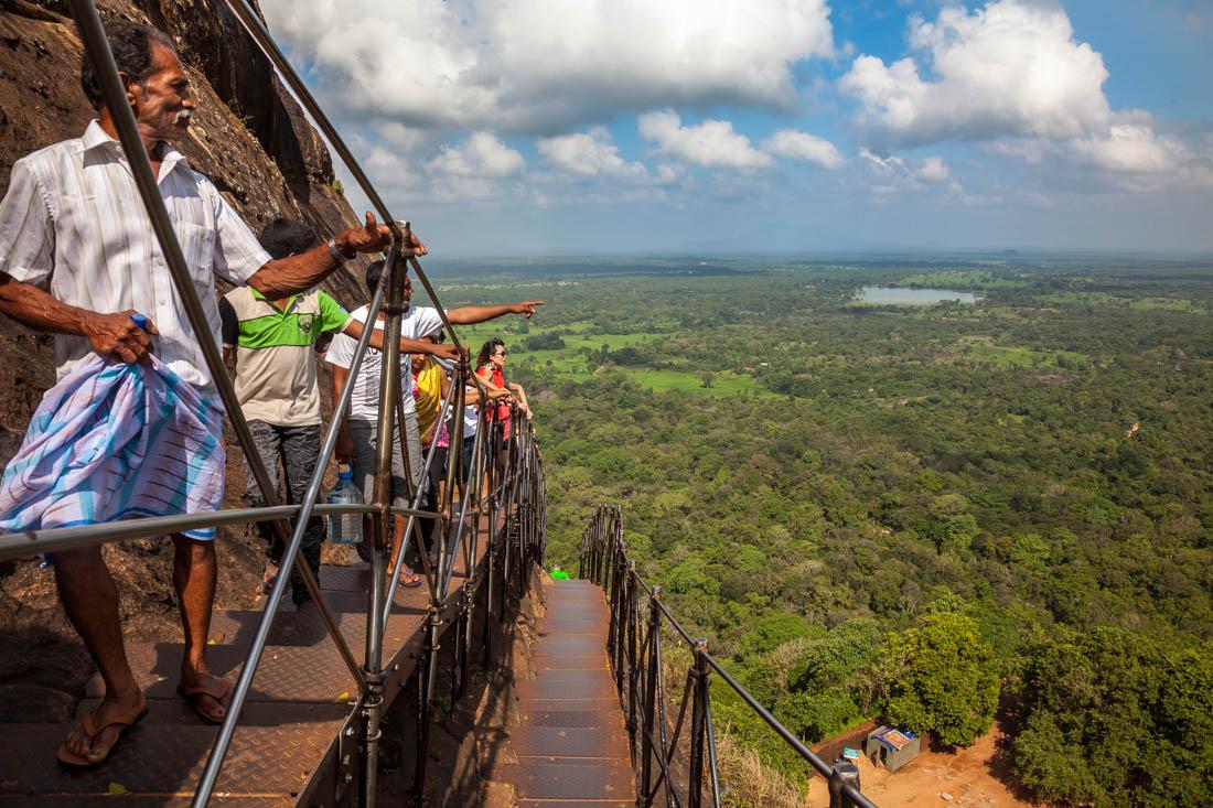 Pessoas a subir escadas metálicas do rochedo de Sigiriya no Sri Lanka.