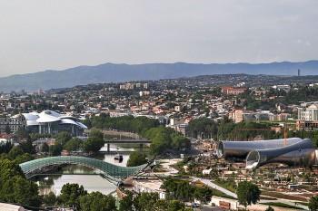 Vista da cidade de Tbilisi, na Geórgia, com rio Kura e estruturas modernistas.
