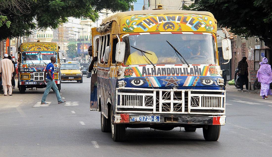 Autocarros coloridos e pessoas nas ruas de Dakar, Senegal.