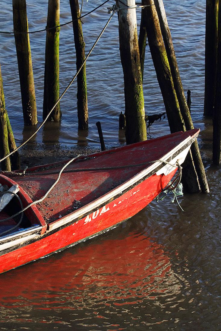 Barco vermelho ancorado junto às estacas de um dos pontões do cais palafítico da Carrasqueira.