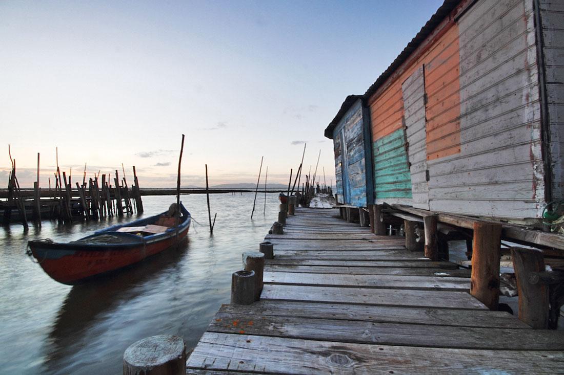 Barco de pesca junto ao pontões e armazéns do cais palafítico da carrasqueira.
