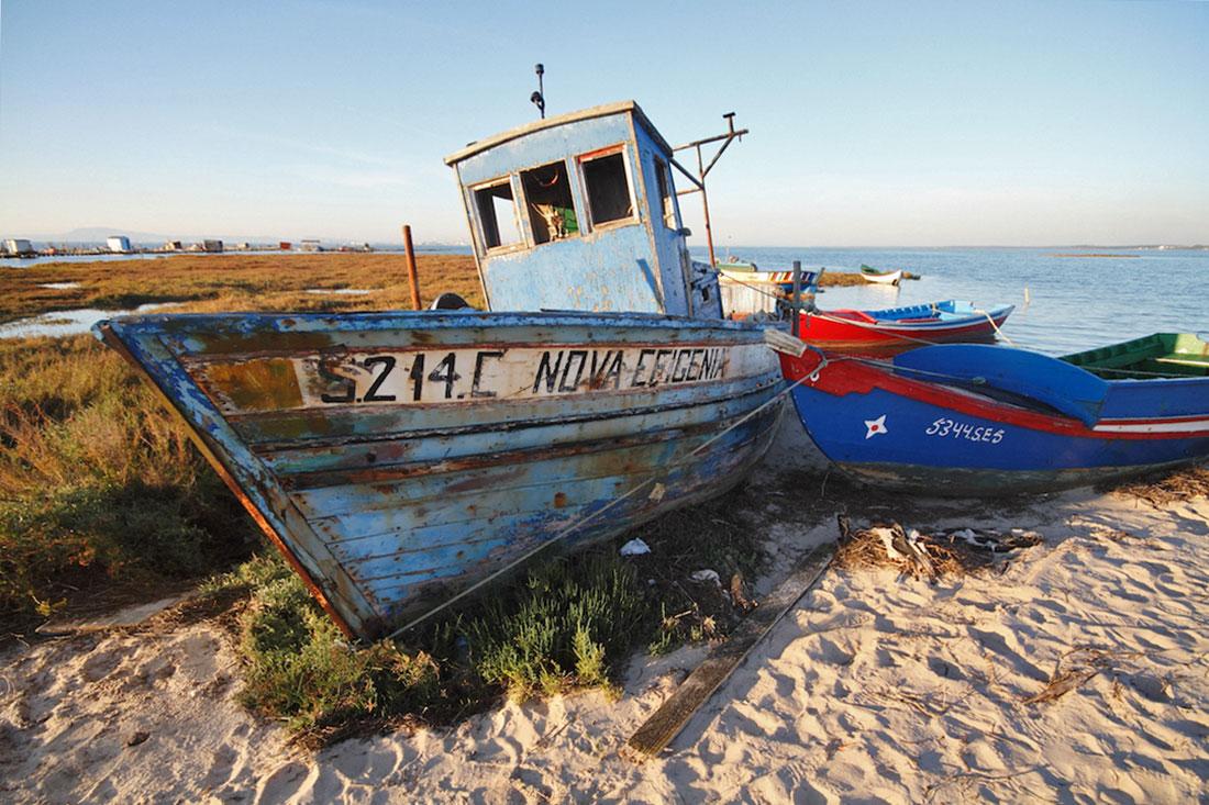 Barcos de pesca abandonados numa praia da Carrasqueira.