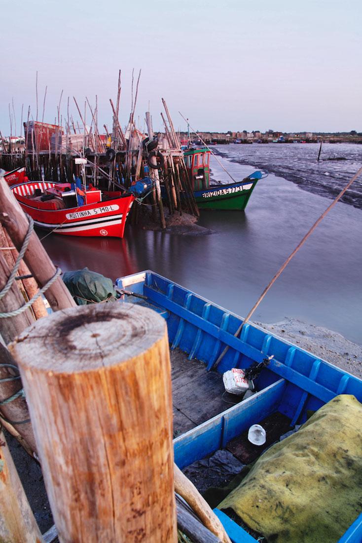 Barcos de pesca, redes, estacas e pontões desorganizados formam o Cais Palafítico da Carrasqueira.