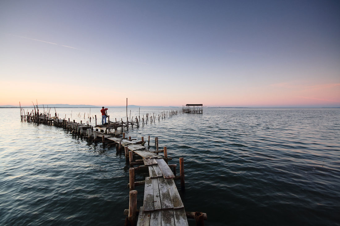 Um fotógrafo prepara-se para fazer uma foto nos pontões do cais palafítico da Carrasqueira.