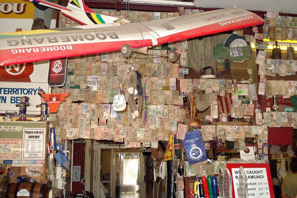 Notas de vários países e avião agarrados a uma das paredes do interior do Daly Waters Pub.