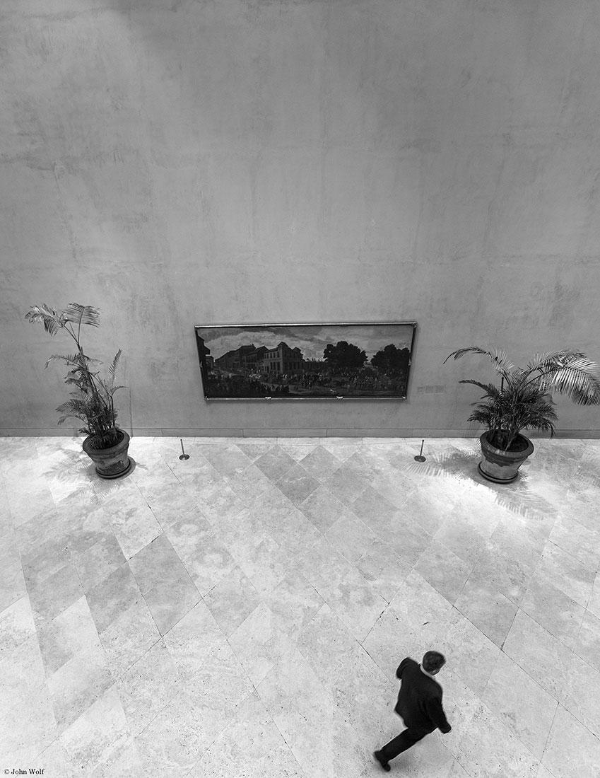 Quadro entre vasos com plantas e um homem a caminhar no museu Thyssen-Bornemisza.