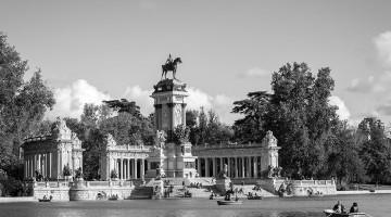 Barcos a remos junto a grande escultura no lago do Parque do Retiro em Madrid.