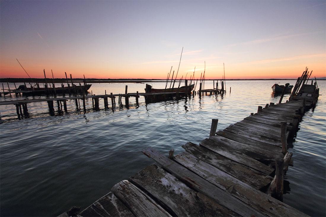 Pontões artesanais de madeira estendem-se rio adentro no cais palafítico da Carrasqueira, em pleno Estuário do Sado.