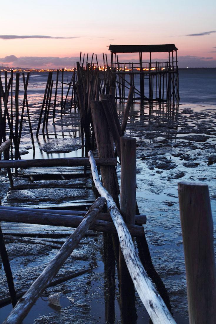 Pôr-do-sol desde um pontão em ruínas no cais palafítico da Carrasqueira com maré baixa.