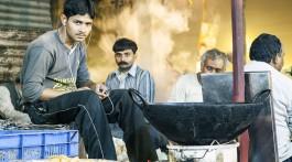 Rapaz a ouvir musica numa banca para comer na rua, Índia.