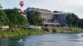 Hotel e balão de ar quente junto ao rio Nam Song, onde navega uma canoa, na cidade de Vang Vieng, Laos.