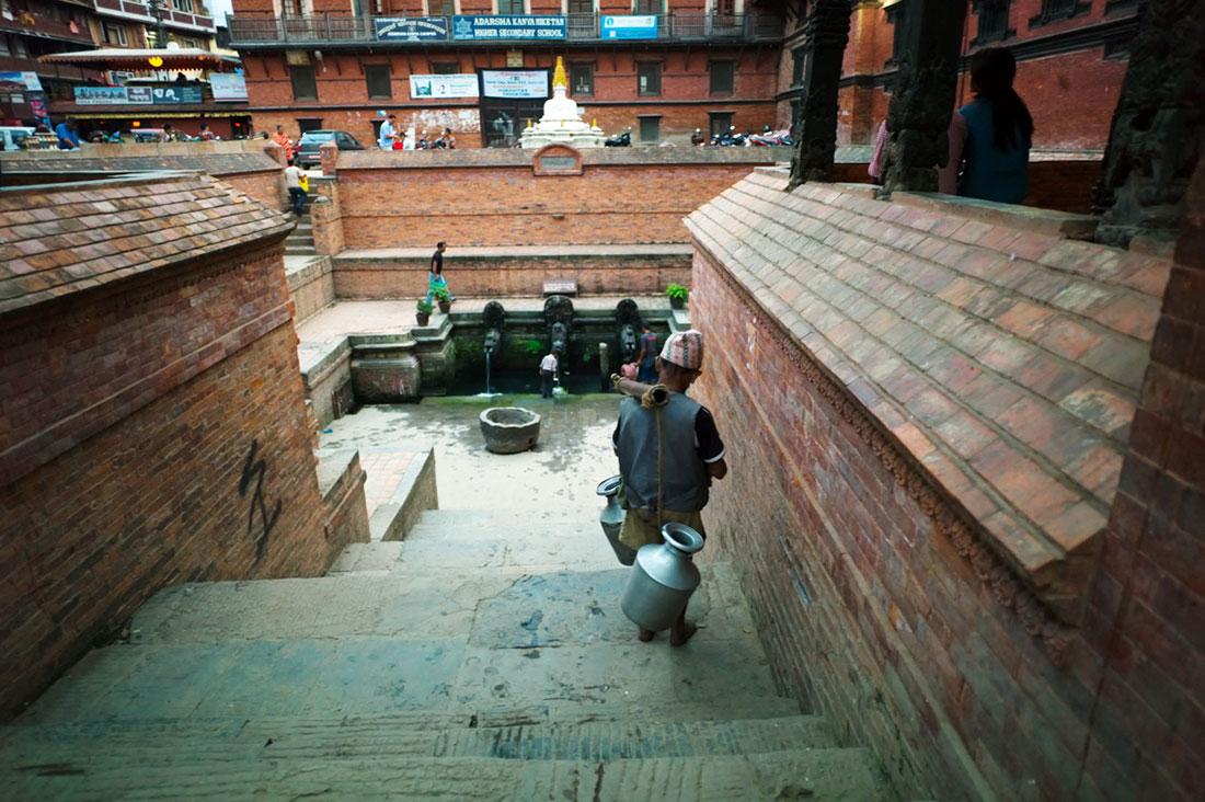 Aguadeiro dirige-se a uma fonte para recarregar água sagrada que irá depois vender pelas ruas de Kathmandu.