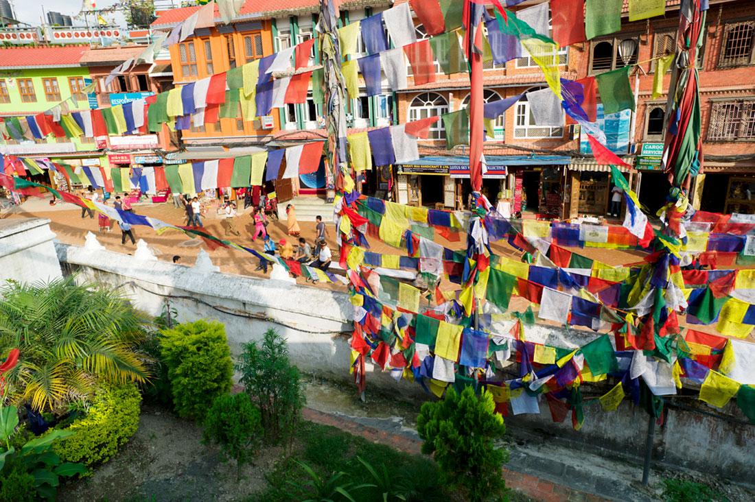 Bandeiras de oração budista esvoaçam por sobre as ruas da cidade de Kathmandu.