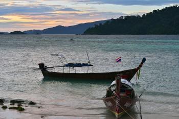 Barcos de pesca ancorados junto a uma praia da ilha Koh Lipe na Tailândia.