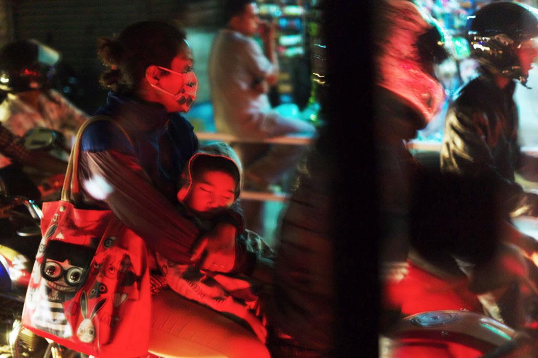 Mulher com criança adormecida ao colo, na traseira de uma mota e no meio do trânsito caótico de Kathmandu.