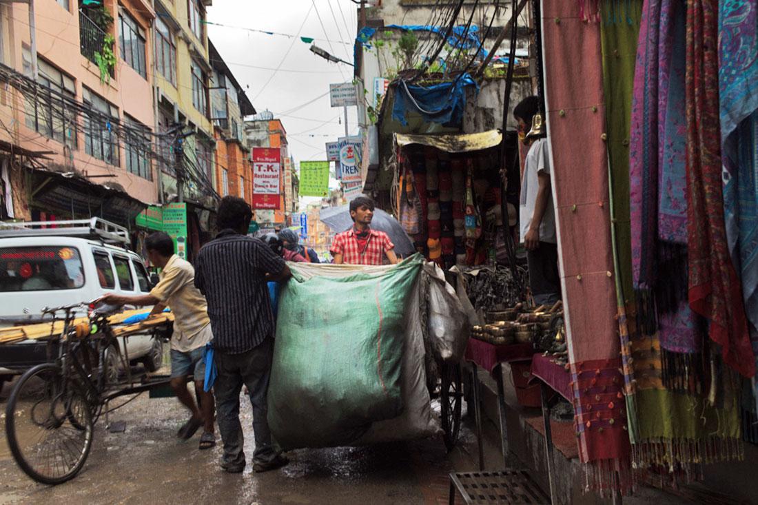 Numa das ruas de Kathmandu procede-se à descarga de um grande saco com mercadoria para vender.