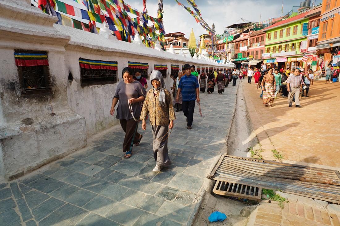 Pessoas caminham em oração ao redor da Boudhanath Stupa em Kathmandu.