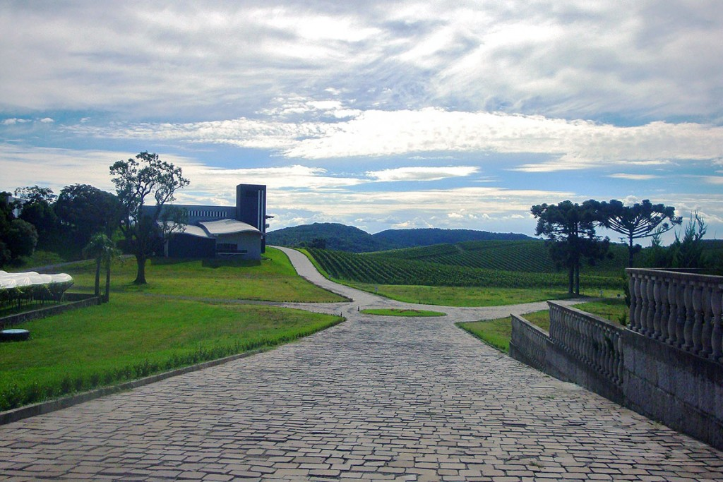 Estrada em pedra basáltica e campos verdes na vinícola Luiz Argenta, em Flores da Cunha, Brasil.
