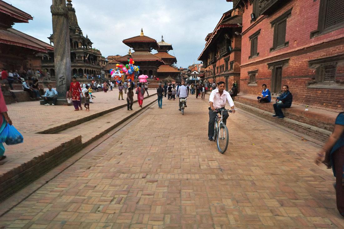 Homem de bicicleta e varias pessoas a caminhar na Praça Durbar em Kathmandu.