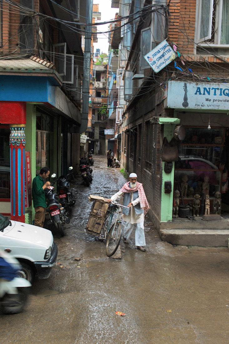Homem conduz manualmente a sua bicicleta através de rua lamacenta em Kathmandu.