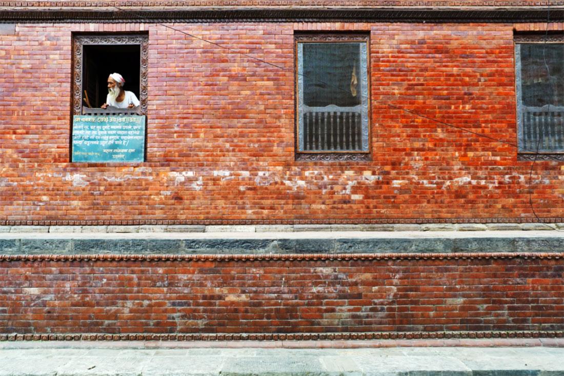 Homem Hindu espreita por uma janela de um prédio de tijolo em Kathmandu.