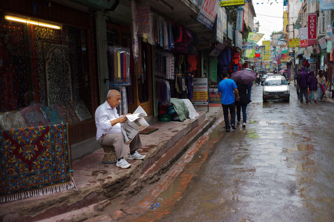 Vendedor de tapetes a ler jornal frente à sua loja em Kathmandu.