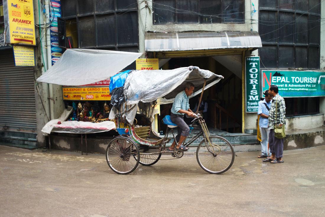 Homem pedala no seu riquexó numa rua antiga de Kathmandu.