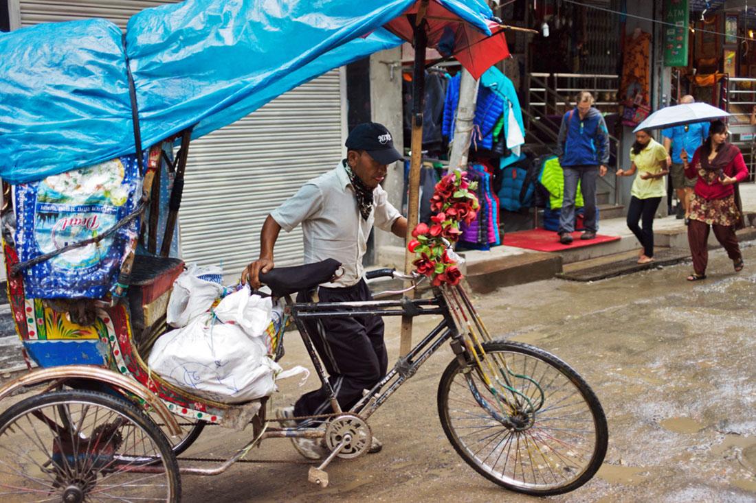Homem conduz o seu riquexó à mão cheio de mercadoria para venda.