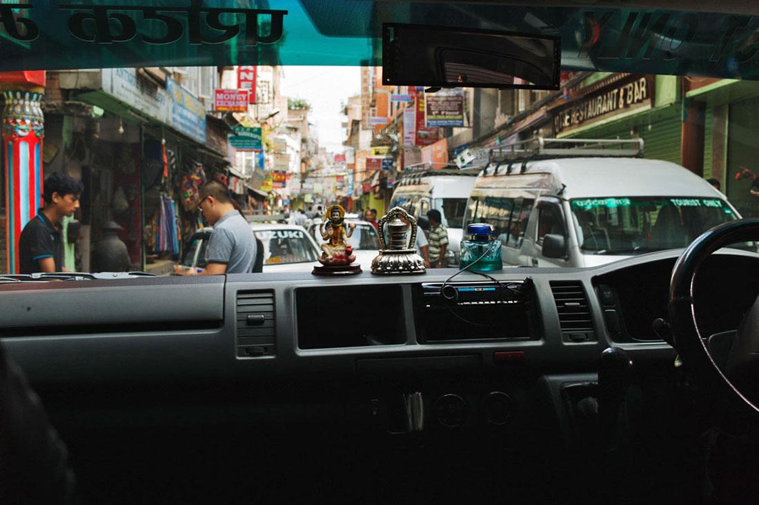 Vista do interior de um táxi em rua congestionada de Kathmandu.