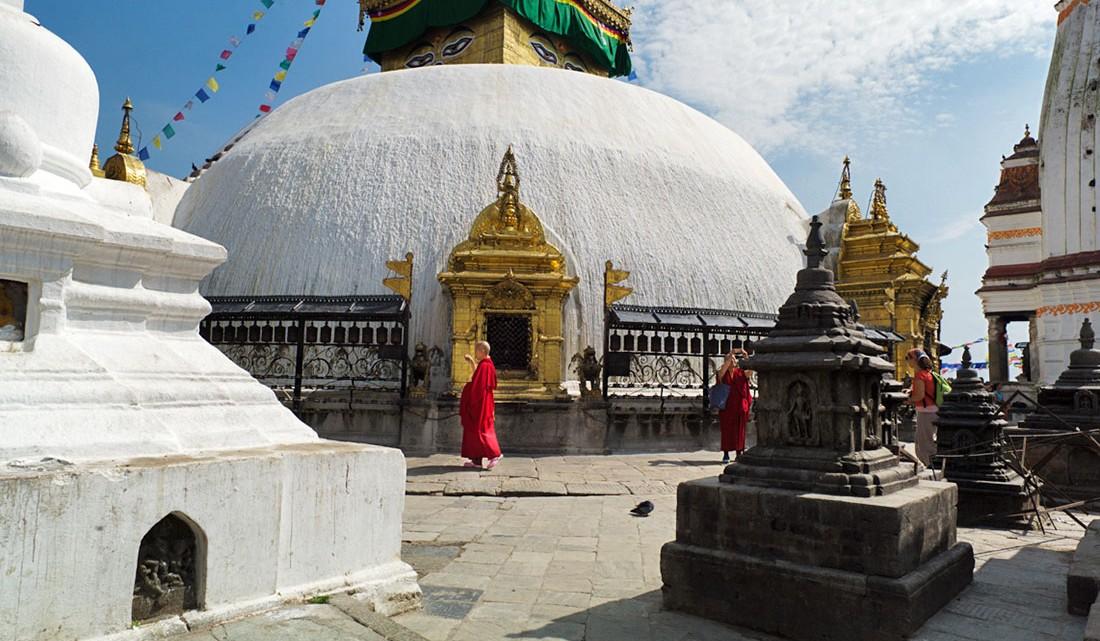 Monges budistas caminham em redor da Boudhanath Stupa em Kathmandu.