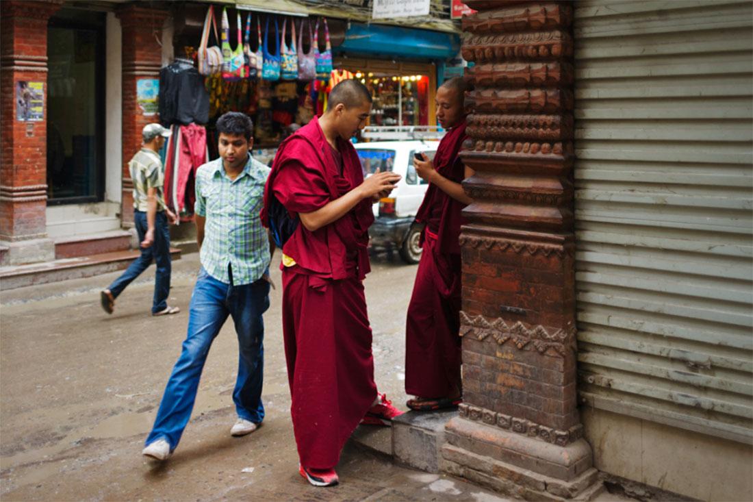 Monges budistas escrevem mensagens nos telemóveis numa esquina da cidade antiga de Kathmandu.